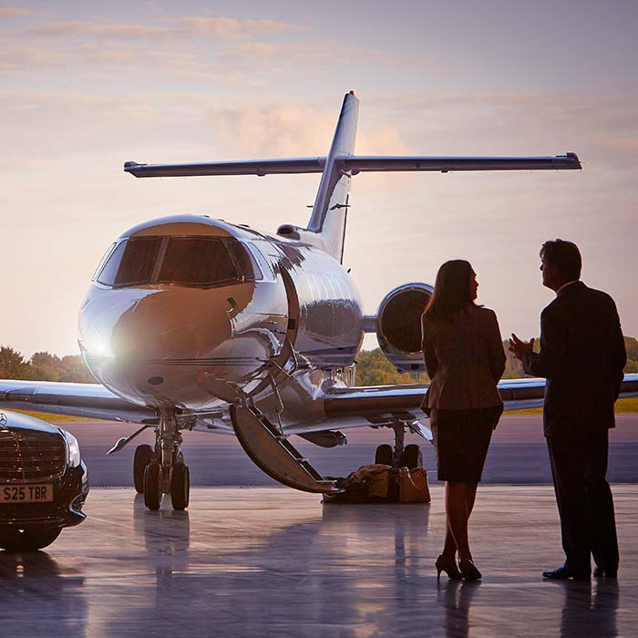 Man and woman walking toward private jet